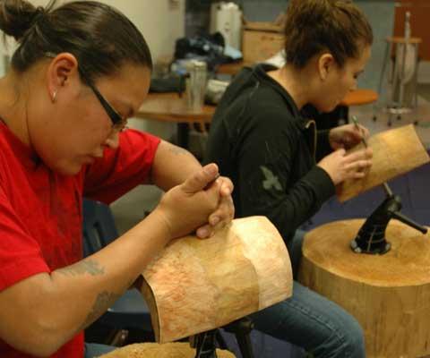Deux femmes artistes autochtones taillent une sculpture en bois.