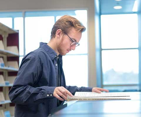 Un étudiant regarde à une partition de musique dans la bibliothèque.