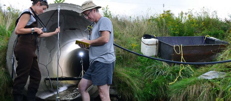 A female and male researcher doing tests near a round ciment culvert.