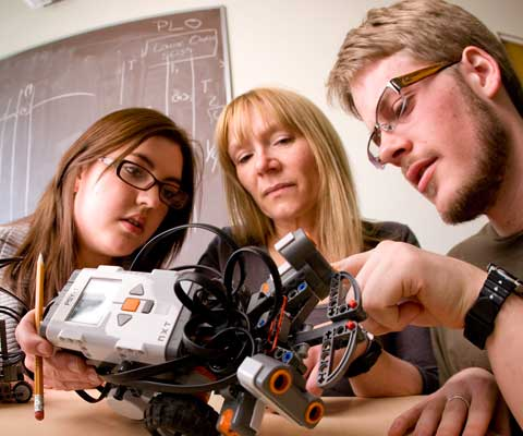 A female and male student with their professor looking at a part of a robot.