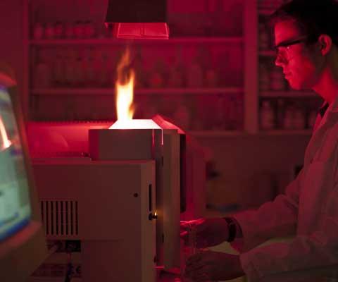 Un chercheur regarde une flamme dans un laboratoire sombre.