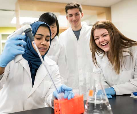 Trois jeunes chercheuses et un jeune chercheur rient et travaillent dans un laboratoire.