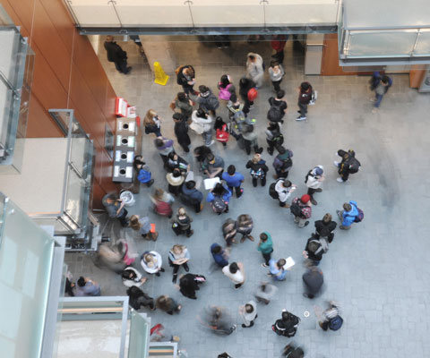 An overview of students gathering in the lobby of a university building.