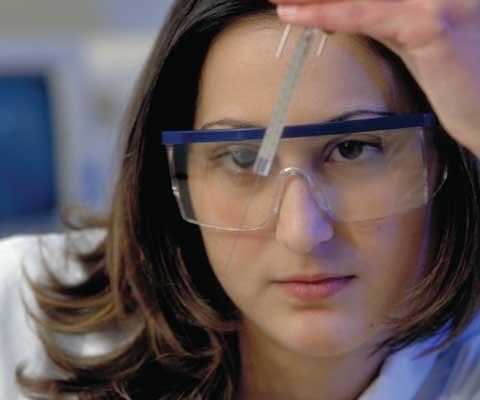 Jeune chercheuse portant des lunettes protection regarde une aiguille.