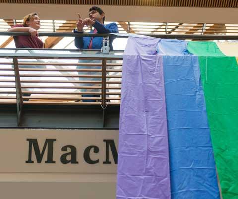 Une étudiante et un étudiant en arrière d'un garde-corps d'où flotte le drapeau arc-en-ciel.