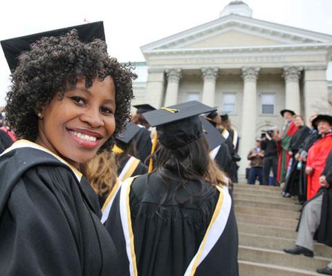 Étudiante noire souriante habillée en toge faisant la queue lors de la cérémonie de la remise des diplômes.