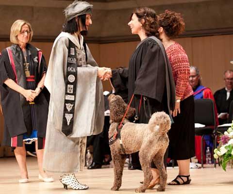 Une étudiante aveugle avec son chien-guide serre la main de la rectrice de l