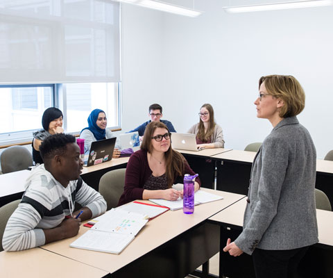 A female professor addresses a classroom of diverse university students.