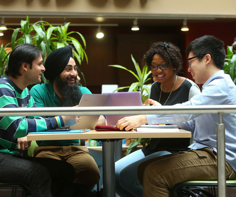 Students from different ethnic backgrounds study together at a cafeteria table.