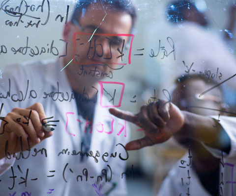 Two researchers writing math formulas on a plexiglass board.