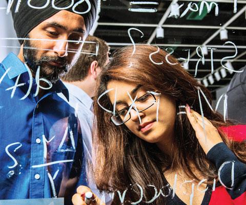 Un chercheur et une chercheuse travaillent des formules mathématiques sur du plexiglas.