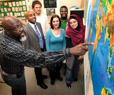 Un chercheur africain pointe son doigt sur une carte mondiale affichée au mur devant un petit groupe d