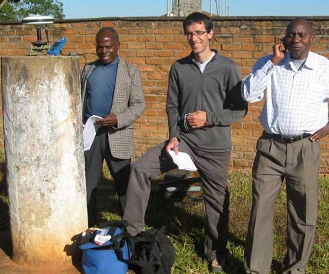 Un chercheur blanc avec ces deux collègues africains prennent des notes et font de la recherche à l