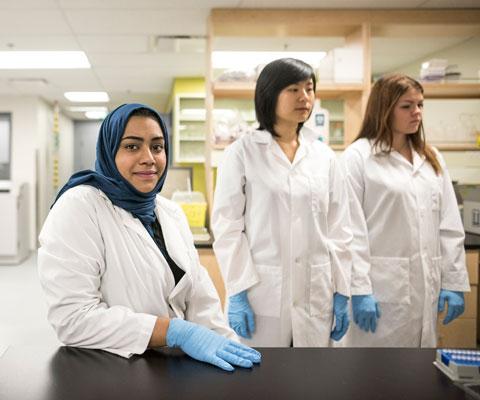 Trois chercheuses portant des blouses de laboratoires blanches sont debouts dans un laboratoire.
