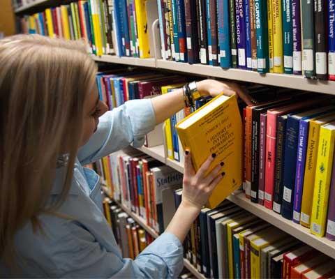 Une jeune femme place un livre sur les rayons dans la bibliothèque.