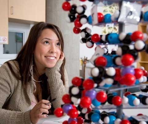 Étudiante autochtone regarde à un modèle à billes et à rayons dans un laboratoire.