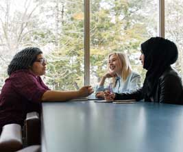 Three female students having a discussion at a table.