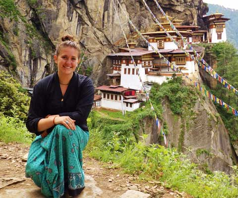 Smiling female student in front of hillside village in Bhutan.