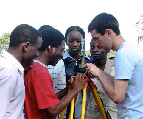 A Canadian student with colleagues in Africa looking at a tripod.