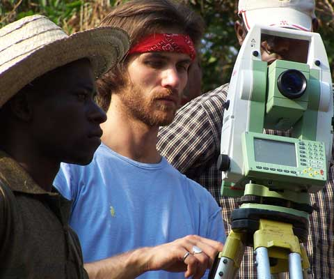 Canadian and African researchers using a surveying tool in the field.