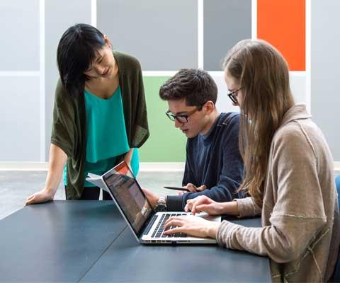Trois étudiants travaillent devant un ordinateur portable.