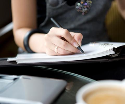 Un gros plan sur une main qui écrit dans un carnet.