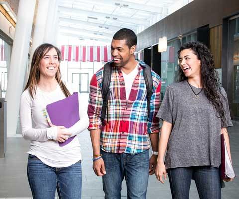 Trois étudiants souriants marchent dans un couloir.