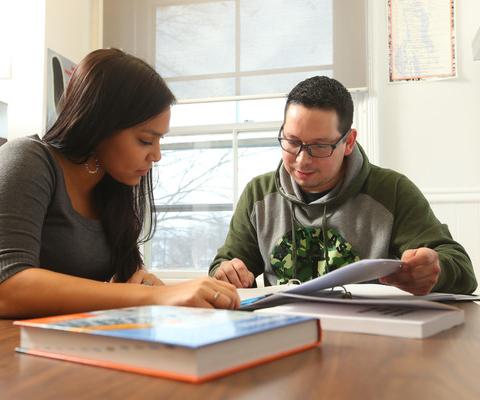 Deux employés autochtones évaluent des formulaires de demande.