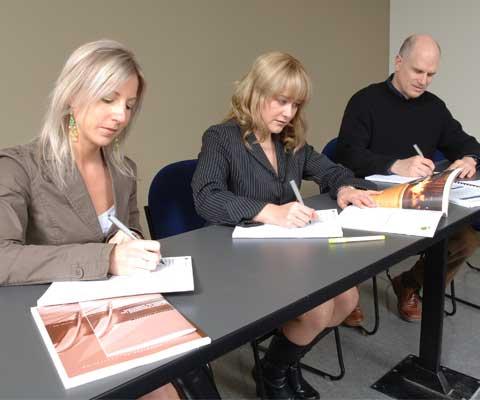 Trois adultes révisent des demandes de bourses d'études.
