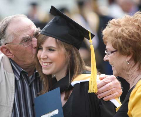 Grandfather kissing his grand daughter's cheek at her convocation ceremony.