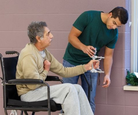 Male student testing a hand strength instrument with an elderly man in a wheelchair.