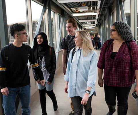 Five students walk down a hallway on campus together.