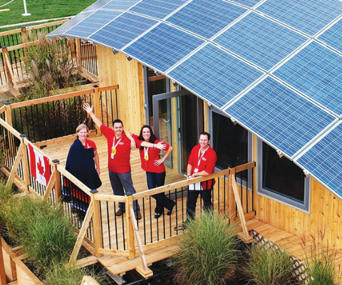 Four people standing on the balcony of a building with a rooftop covered entirely in solar panels.