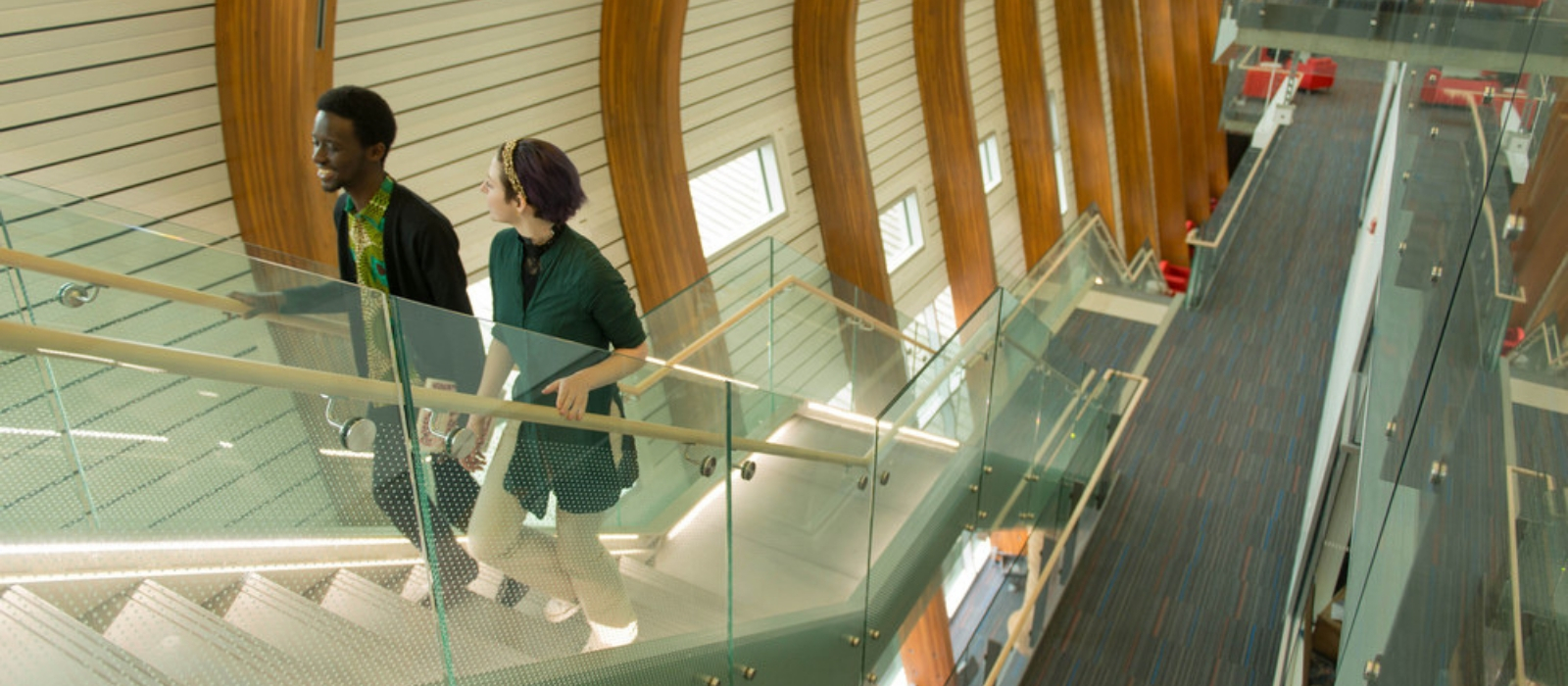 Two students walk up the stairs in a university building.