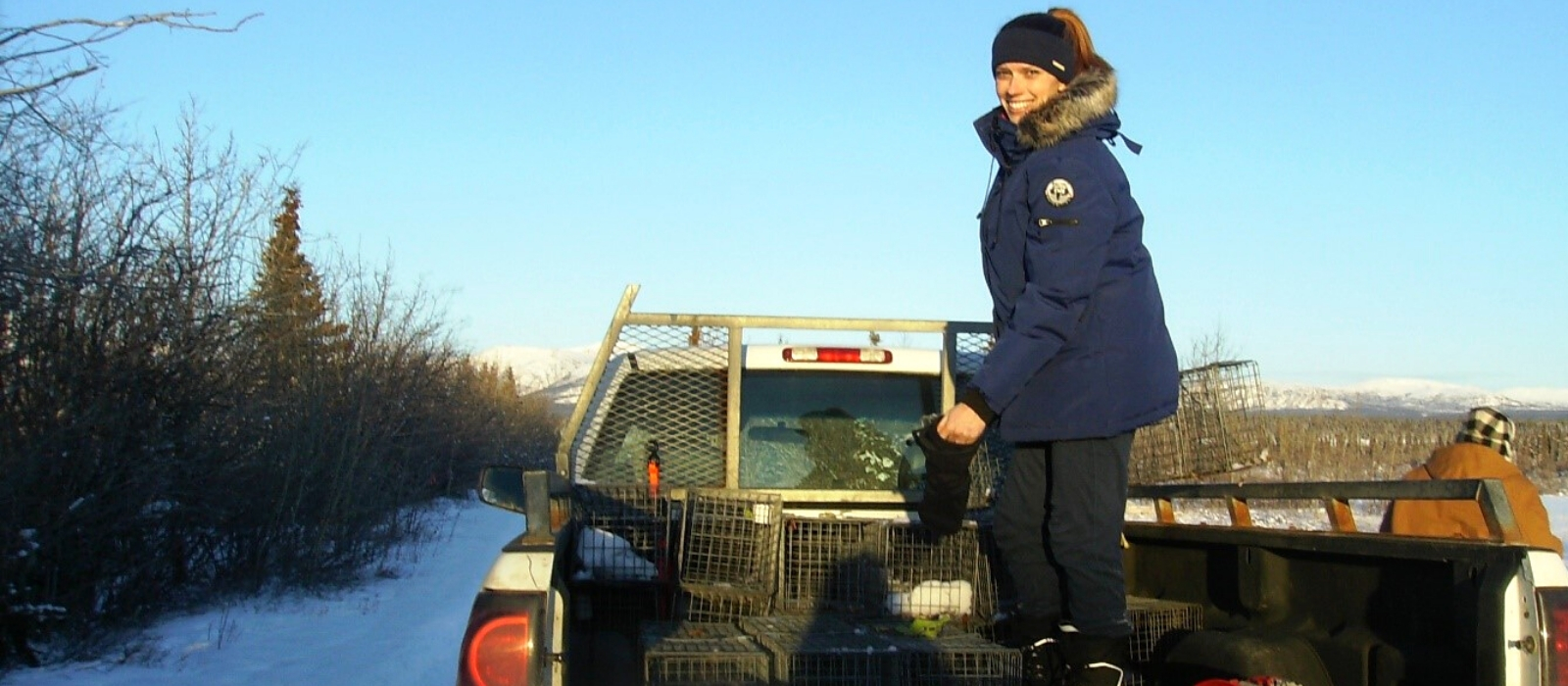 A female researchers stands in the back of a pick-up truck in Canada