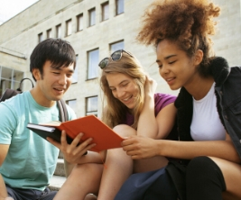 Three students of different ethnicities sit on the steps outside a university building reading a book together.