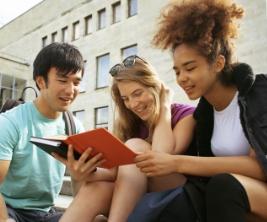 Trois étudiants de différentes origines sont assis sur les marches à l'extérieur d'un bâtiment universitaire en train de lire un livre ensemble.