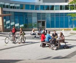 Des étudiants marchent devant un édifice moderne sur un campus.