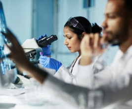 Two researchers wearing white lab coats conduct medical research in a laboratory.