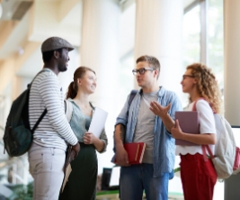 A group of four university students stand in a circle inside a university building talking.