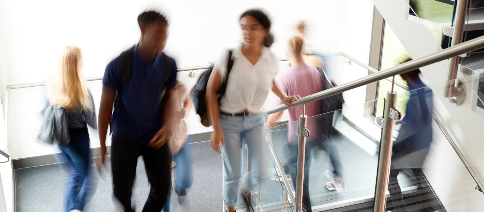 A busy university hallway filled with blurred images of students.