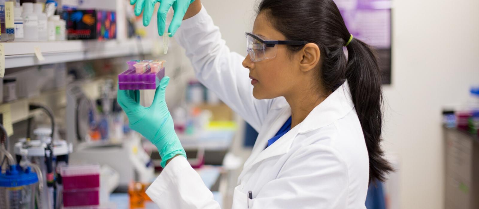 Une chercheuse portant des gants de sécurité et une blouse de laboratoire se tient dans un laboratoire et utilise un compte-gouttes pour déposer du liquide dans un petit récipient.