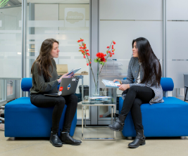 Two female students sit talking to one another in an office setting.