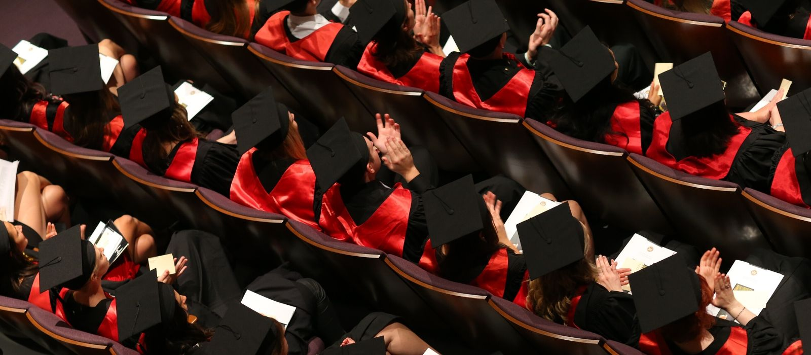 An aerial view of university graduates sitting in an auditorium wearing graduation caps, gowns and red sashes.