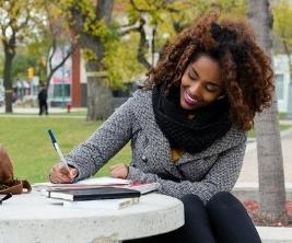 Sur un campus universitaire, une jeune femme étudie à une table extérieure.