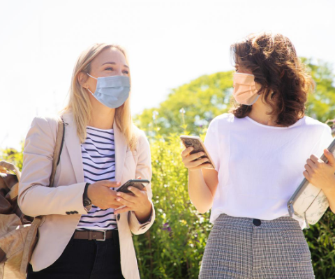 Two female university student wearing face masks walk next to one another outside while talking and holding their cell phones.