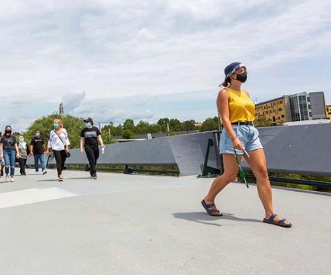 A group of university students wearing masks and face coverings walk across a bridge on the Trent University campus.