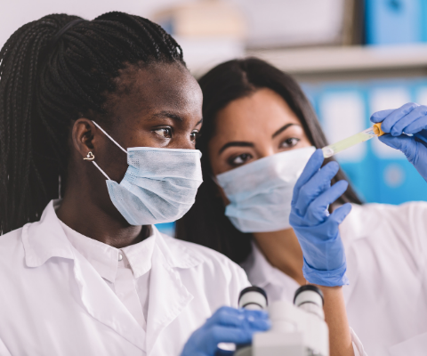 Two women with masks and gloves working in a lab