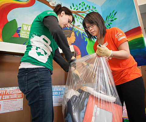 Two students putting items into a recycling bag.